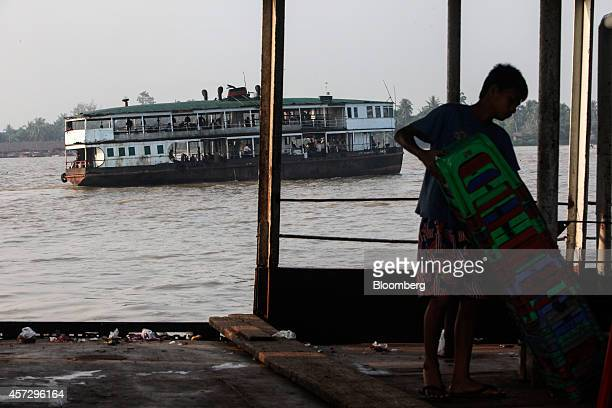 A worker arranges stools on a boat as a commuter ferry travels along the Yangon river in Yangon Myanmar on Tuesday Oct 14 2014 Myanmars economy is...