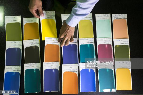 A worker arranges the results of a spread test in a laboratory at an Akzo Nobel India Ltd paint factory in Gwalior Madhya Pradesh India on Thursday...