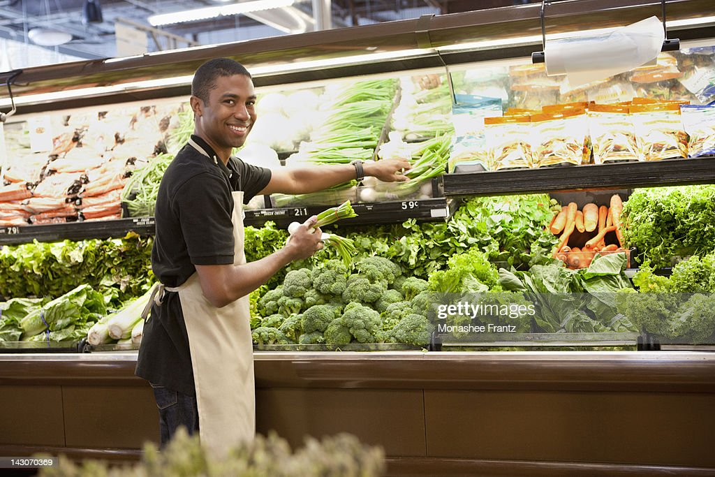 Worker arranging produce in supermarket : Stock Photo
