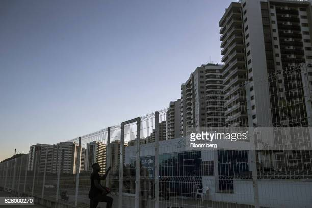 A worker arrives at a Companhia Estadual de Aguas e Esgotos plant built to serve the Ilha Pura property604 empty luxury apartments used by more than...