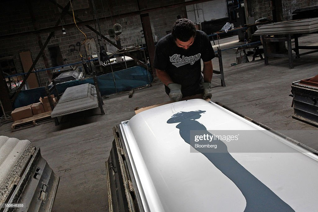 A worker assembles a burial vault cover at the American Wilbert Vault Corp. manufacturing facility in Des Plaines, Illinois, U.S., on Thursday, Aug. 23, 2012. Several U.S. Presidents including John F. Kennedy and Ronald Reagan, and other famous people including Al Capone, Louis Armstrong, Elvis Presley and Frank Sinatra are buried in American Wilbert burial vaults, according to the company. The U.S. Census Bureau is expected to release data on orders for durable goods on Aug. 24. Photographer: Tim Boyle/Bloomberg via Getty Images