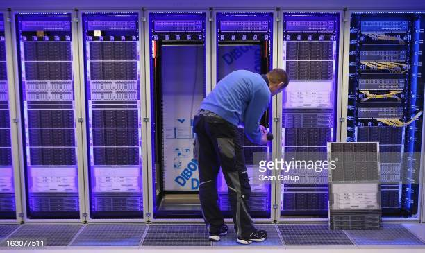 A worker assembles a data center module container at the Rittal stand at the 2013 CeBIT technology trade fair the day before the fair opens to...