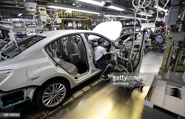 A worker assembles a Fuji Heavy Industries Ltd Subaru XV vehicle on the production line at the company's Gunma Yajima Plant in Ota City Gunma...