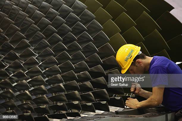 A worker assembles a gas turbine at the Siemens gas turbine factory on January 8 2010 in Berlin Germany Recent economic data including...