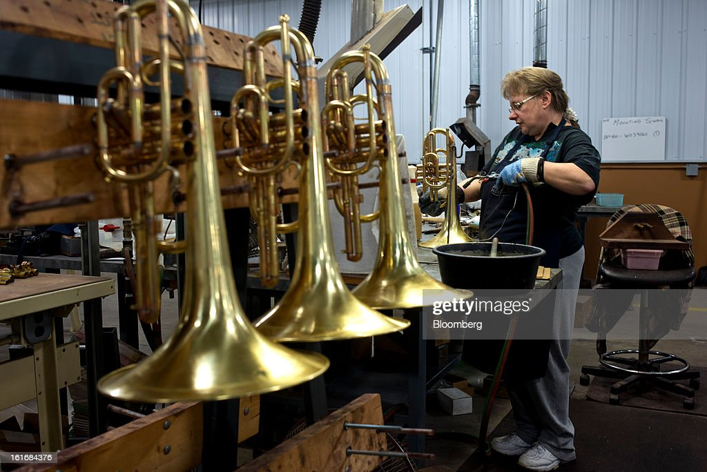 A worker assembles a mellophone in the manufacturing department of the E.K Blessing Co. in Elkhart, Indiana, U.S., on Thursday, Feb. 7, 2013. Photographer: Ty Wright/Bloomberg via Getty Images