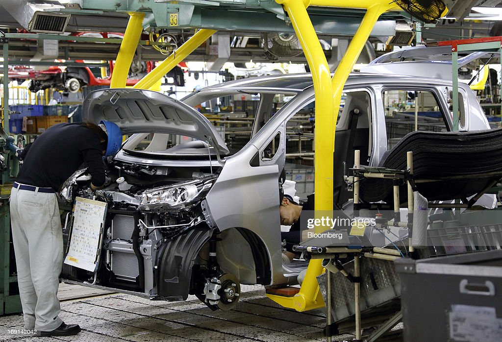 A worker assembles a minicar which will be sold as the Nissan DAYZ by Nissan Motor Co. and Mitsubishi eK Wagon by Mitsubishi Motors Corp. on the production line of the Mitsubishi Motors Mizushima plant in Kurashiki City, Okayama Prefecture, Japan, on Monday, May 20, 2013. Nissan will start selling the first minicar it jointly developed with Mitsubishi Motors in Japan next month amid increasing demand from the nation's consumers for smaller and cheaper vehicles. Photographer: Tomohiro Ohsumi/Bloomberg via Getty Images