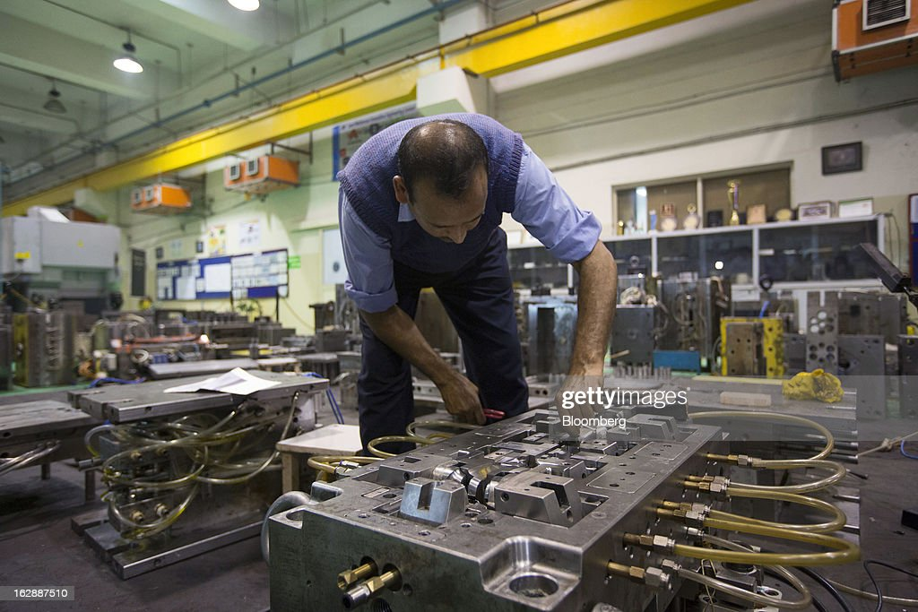 A worker assembles a mold at the Motherson Sumi Systems Ltd. (MSSL) injection molding plant in Noida, India, on Thursday, Feb. 28, 2013. Motherson Sumi Systems Ltd., 25 percent owned by Sumitomo Electric Industries Ltd. and India's biggest auto parts maker, supplies rear view mirrors, bumpers and body panels to clients including Porsche Automobil Holding SE, Bayerische Motoren Werke AG and Volkswagen AG. Photographer: Brent Lewin/Bloomberg via Getty Images