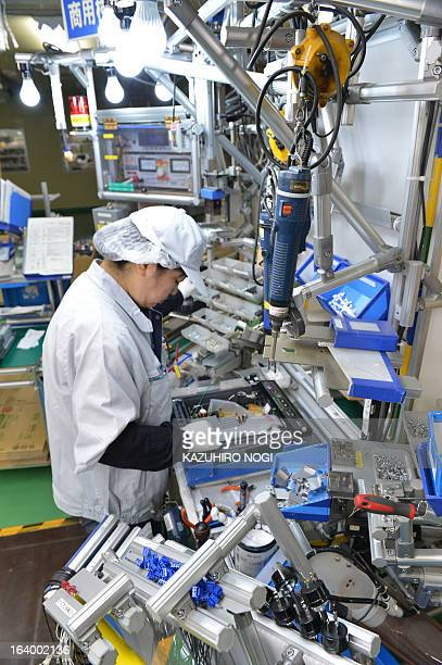 A worker assembles a new IH cooking heater on cellular manufacturing at Japan's Hitachi Appliances Inc Taga Works in Hitachi about 150 km east of...