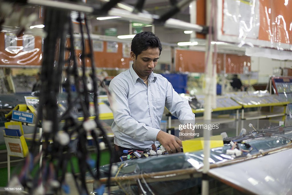A worker assembles a wire harness at the Motherson Sumi Systems Ltd. wiring harness plant in Faridabad, India, on Thursday, Feb. 28, 2013. Motherson Sumi Systems Ltd., 25 percent owned by Sumitomo Electric Industries Ltd. and India's biggest auto parts maker, supplies rear view mirrors, bumpers and body panels to clients including Porsche Automobil Holding SE, Bayerische Motoren Werke AG and Volkswagen AG. Photographer: Brent Lewin/Bloomberg via Getty Images