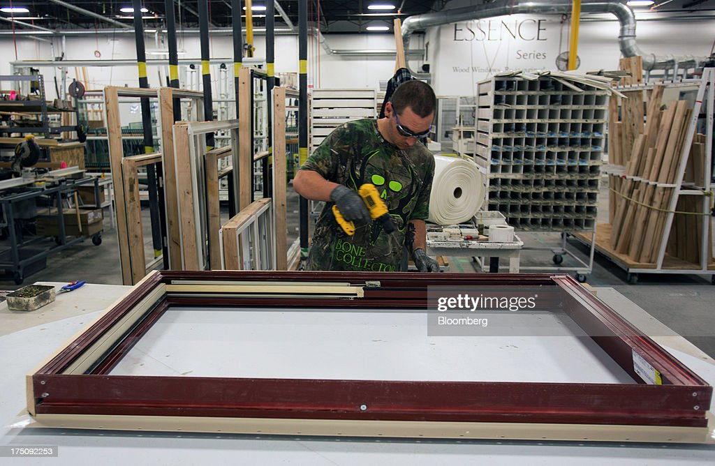 A worker assembles a wood window frame at the Milgard Windows & Doors' manufacturing facility in Tacoma, Washington, U.S., on Wednesday, July 24, 2013. The U.S. Census Bureau is scheduled to release monthly construction spending figures on Aug. 1. Photographer: Tim Rue/Bloomberg via Getty Images