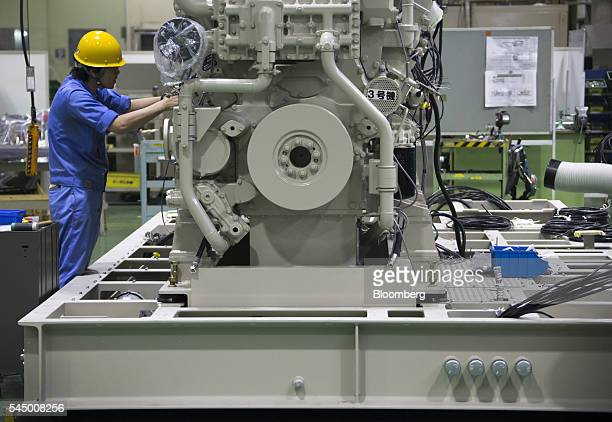A worker assembles an engine at the Mitsubishi Heavy Industries Engine Turbocharger Ltd plant in Sagamihara Kanagawa Prefecture Japan on Monday July...