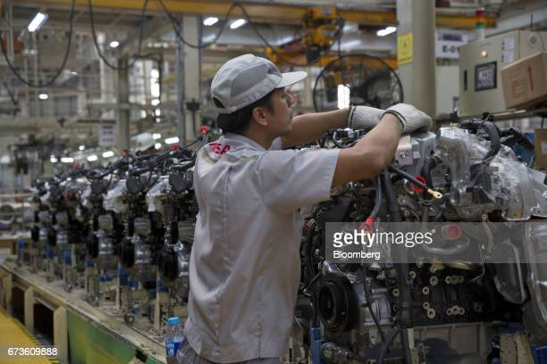 A worker assembles an engine of a Nissan Motor Co Navara pickup truck on an assembly line at the company's plant in Samut Prakan Thailand on Tuesday...