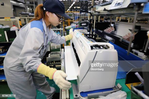 A worker assembles an indoor unit of a Daikin Industries Ltd split type air conditioner on the production line of the company's Shiga plant in...