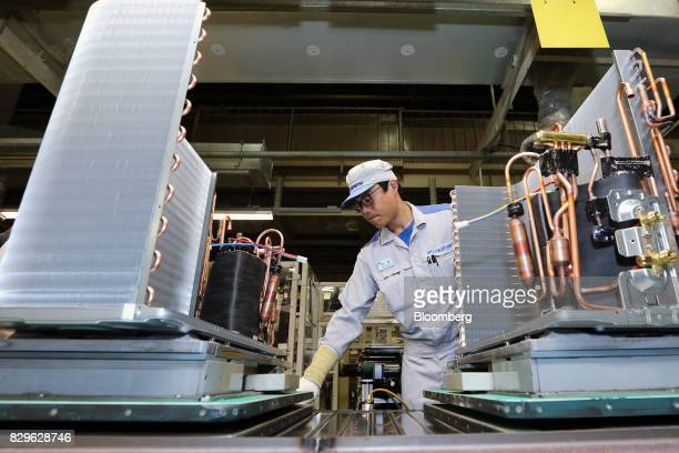 A worker assembles an outdoor unit of a Daikin Industries Ltd split type air conditioner on the production line of the company's Shiga plant in...