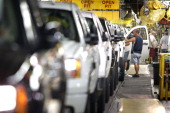 A worker assembles General Motors trucks on the assembly line at the GM Flint Assembly plant July 18 2011 in Flint Michigan GM announced they will be...