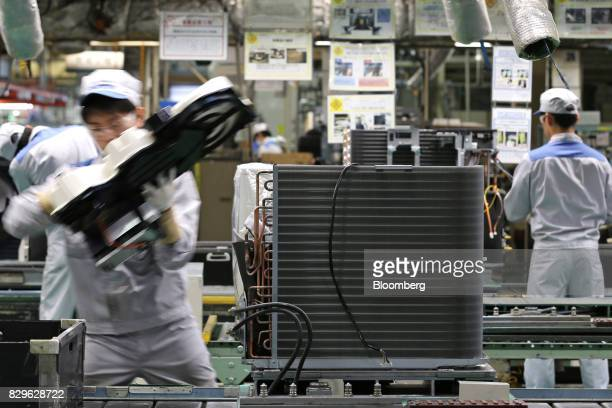 A worker assembles the outdoor unit of a Daikin Industries Ltd split type air conditioner on the production line of the company's Shiga plant in...
