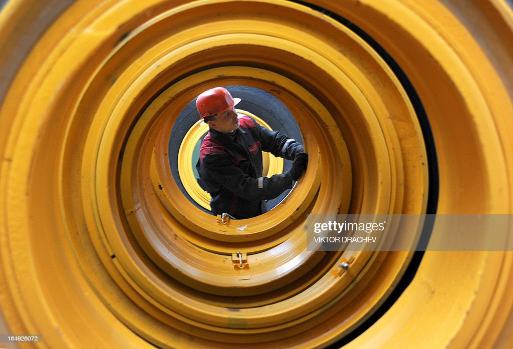 A worker assembleSwheels of a heavy duty BelAZ dump-truck at the assembly department of the BelAZ automobile plant in the Belarus town of Zhodino, some 50km north of Minsk, on March 29, 2013. AFP PHOTO / VIKTOR DRACHEV