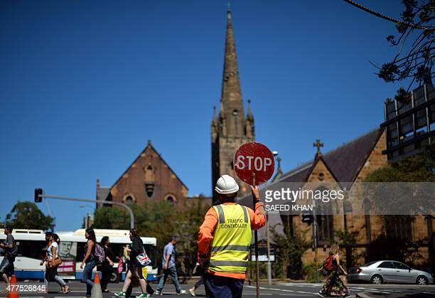 A worker at a construction site directs traffic in front of a church in downtown Sydney on March 10 2014 Australia's economy expanded a...