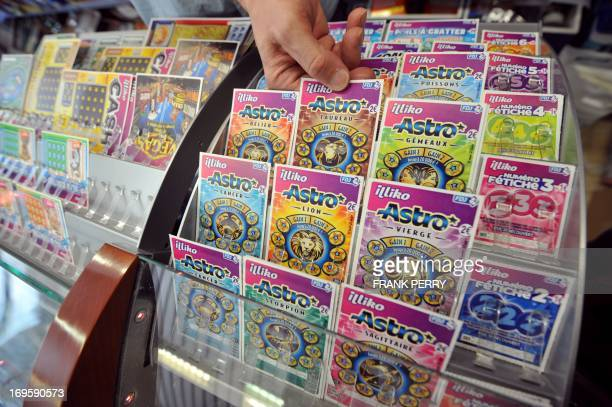 A worker at a tobacconists arranges scratchcards of the Française des Jeux the operator of France's national lottery and scratchcards on the counter...