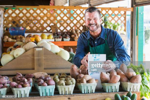 Worker at farmer's market setting up display, price sign