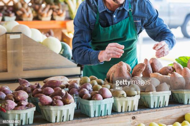 Worker at farmer's market setting up produce stand