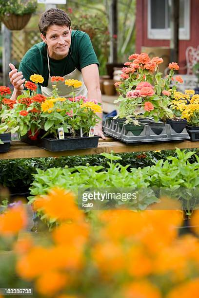 Worker at garden center retail store with flowers