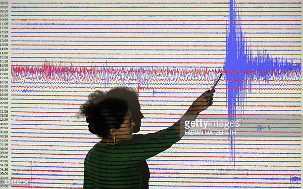A worker at Potsdam's Geophysics Research center points 29 March 2005 to seismograph readings recorded as a massive quake struck off Sumatra's...