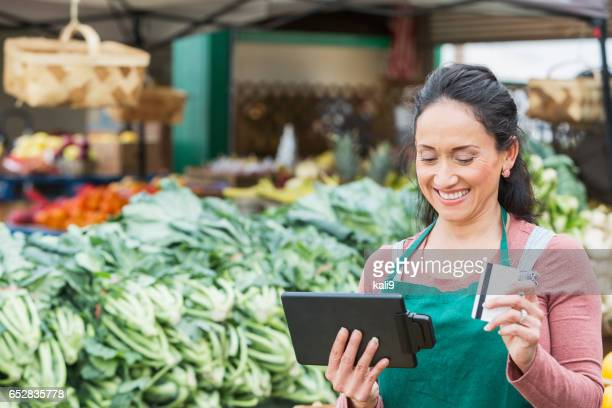 Worker at produce market processing credit card