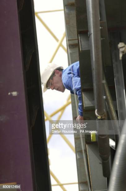 A worker at the Alstom Chantiers de L'Atlantique ship yard in Saint Nazaire Brittany France watch as the keel laying ceromony takes place on the...