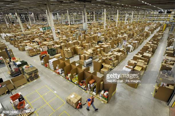 A worker at the Amazon fulfilment centre in Swansea pulls a pump trolley past thousands of cardboard storage bins which hold goods to be shipped all...