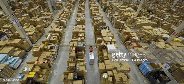 A worker at the Amazon fulfilment centre in Swansea pushes a picker trolley past thousands of cardboard storage bins which hold goods to be shipped...