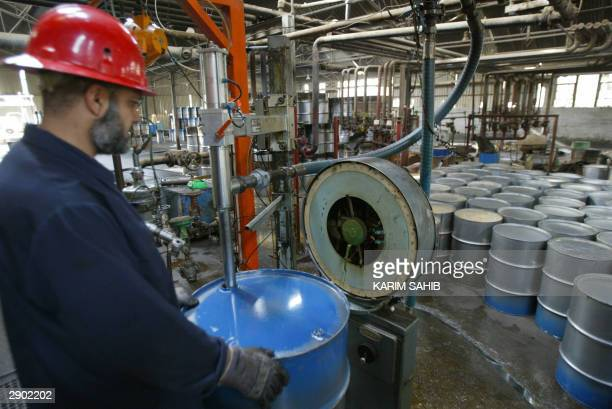 A worker at the Dura oil refinery on the southern outskirts of Baghdad fills a barrel 26 January 2004 Iraq's former dictator Saddam Hussein rewarded...
