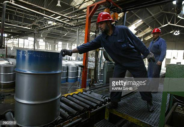 A worker at the Dura oil refinery on the southern outskirts of Baghdad holds a barrel on a conveyor belt 26 January 2004 Iraq's former dictator...
