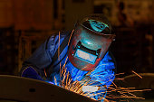Worker at the factory is welding assembly automotive part