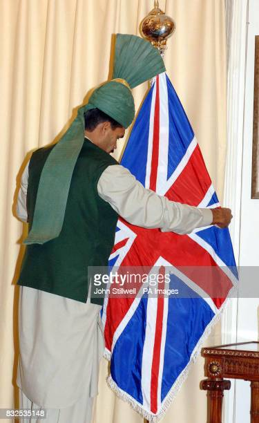 A worker at the Pakistani Prime Minister's official residence in Islamabad adjusts the Union Flag before the arrival of the Prince of Wales and the...