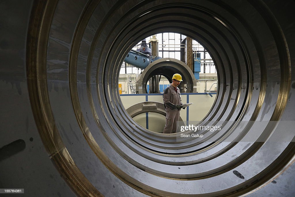 A worker at the photographer's request walks past the casing of a gas turbine at the Siemens gas turbine plant on November 11 2012 in Berlin Germany...