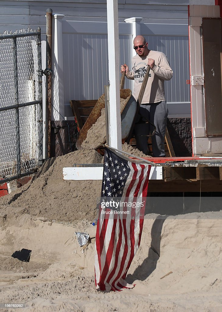 A worker at the Sunny Atlantic Beach Club removes sand from the cabanas on November 20, 2012 in Atlantic Beach, New York. More than three weeks after Superstorm Sandy hit the New York area, residents continue their restoration efforts in many affected areas on Long Island.