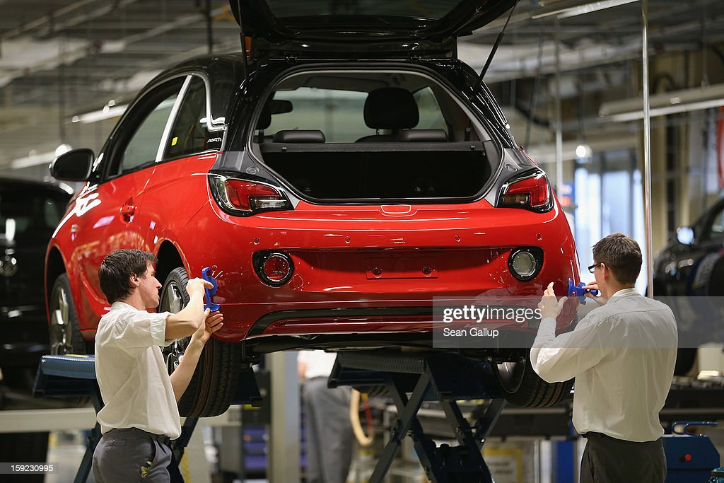 Worker attach spoliers to Opel Adam car next to the assembly line shortly after a celebration to mark the launch of the new Opel compact car at the...