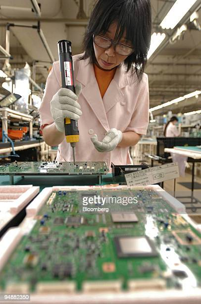 A worker attaches a circuit board for a mobile phone network base station to metal plate at Fujitsu Ltd's Nasu Factory in Tochigi Prefecture Japan...