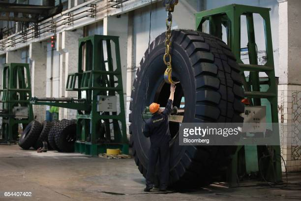 A worker attaches a crane hook to lift a large 4000R57 sized tire in the control room at the Belshina JSC tire factory in Babruysk Belarus on...