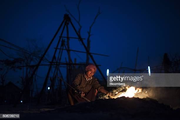 A worker attends to a fire in front of a silhouetted rig at an oil field in Minhla Bago Region Myanmar on Monday Feb 1 2016 The new government of...