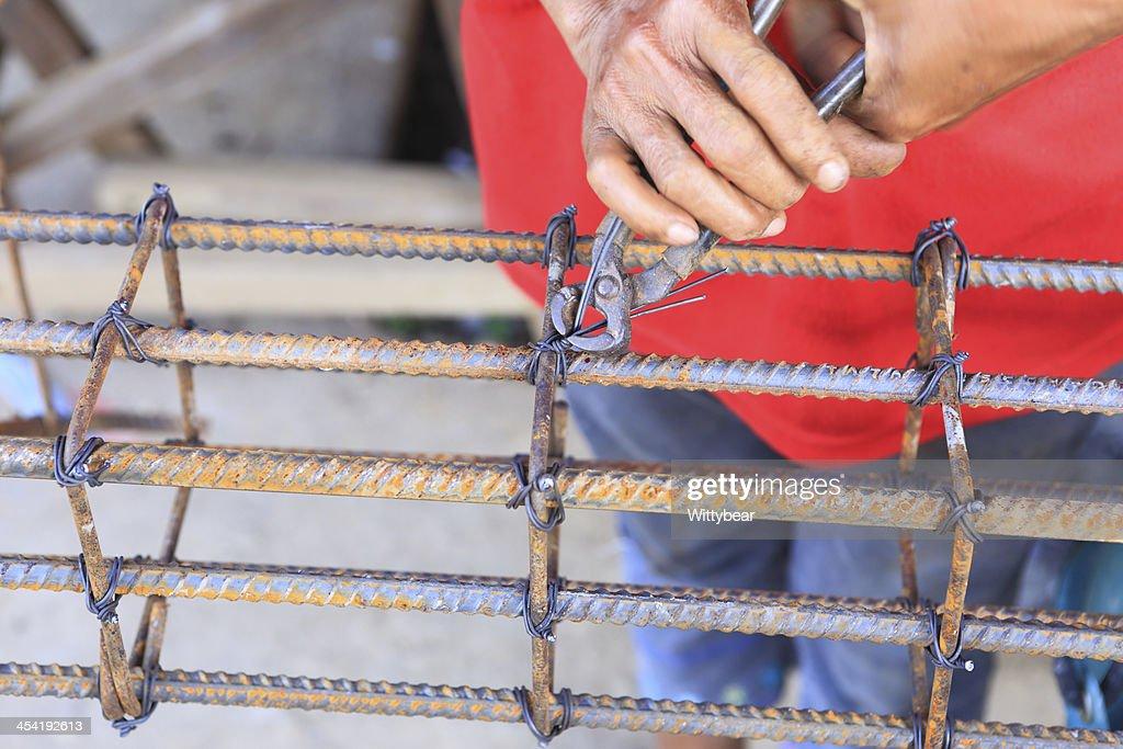 worker bending steel for construction job : Stock Photo
