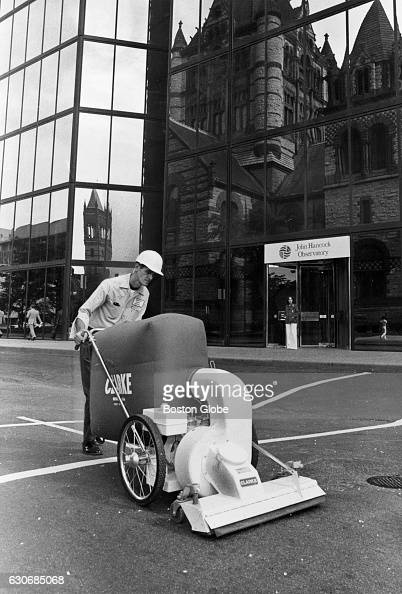 Worker Bill Nee uses a vacuum cleaner to pick up pieces of glass from St James Avenue in Boston after a window on the John Hancock Tower shattered on...