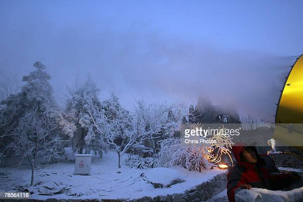 A worker blasts fake snow from a snow machine onto trees in the Firth Forest area of the Happy Valley Amusement Park on December 19 2007 in Beijing...