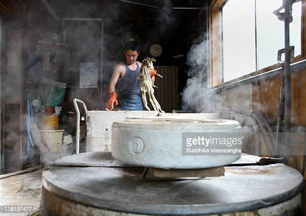 A worker boils the bark of mulberry trees at a mill that makes handmade paper at Iwano Heizaburo Seishi Sho Company in Echizen paper village on July...