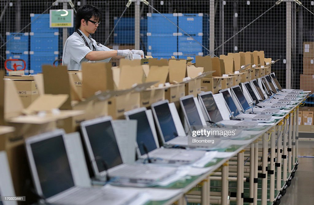 A worker boxes Panasonic Corp.'s Let's Note laptop computers after configuring software systems and programs at the company's plant in Kobe City, Hyogo Prefecture, Japan, on Tuesday, June 11, 2013. Panasonic manufactures electric and electronic products. Photographer: Yuriko Nakao/Bloomberg via Getty Images