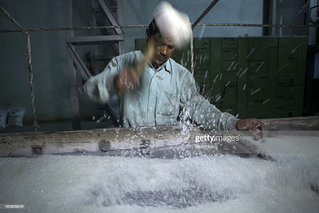 A worker breaks sugar crystals in the crystalized sugar manufacturing unit of the Simbhaoli Sugars Ltd. mill in Ghaziabad, Uttar Pradesh, India, on Tuesday, Feb. 26, 2013. India, the world's biggest sugar producer, plans to seek a consensus among various ministries on ending four-decade old state controls on the domestic industry, Food Minister K.V. Thomas said. Photographer: Prashanth Vishwanathan/Bloomberg via Getty Images