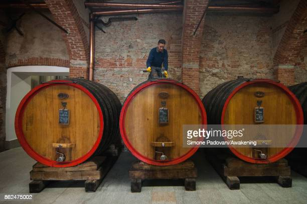 A worker breaks the plug of a barrel with Barolo to check the quality on October 17 2017 in the Barolo region Italy Because of the high summer...