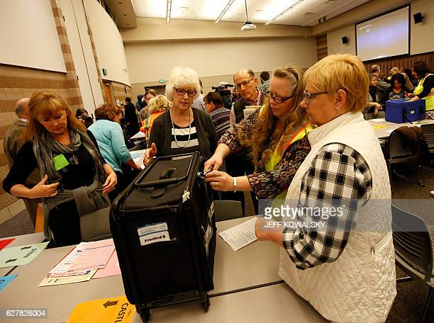 A worker breaks the seal of the containers before the start of the recount of ballots cast in Oakland County Michigan from the 2016 US presidential...