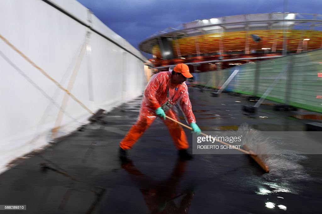TOPSHOT A worker brushes of excess water near the Tennis Center court at the Olympic park in Rio de Janeiro after a constant rain delayed all the...